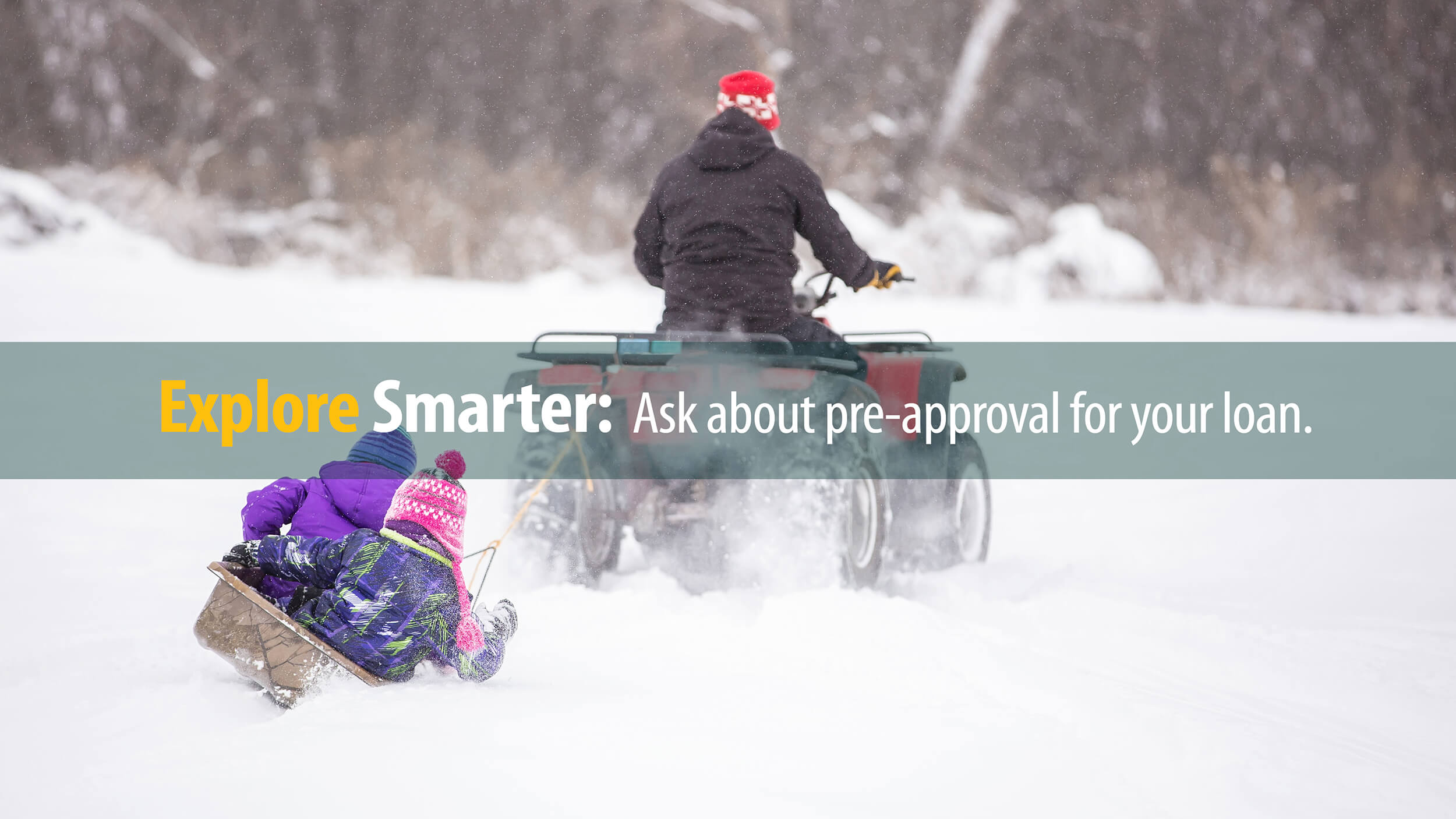 Adult on 4-wheeler purchased with First Source financing tows kids on sled through snow